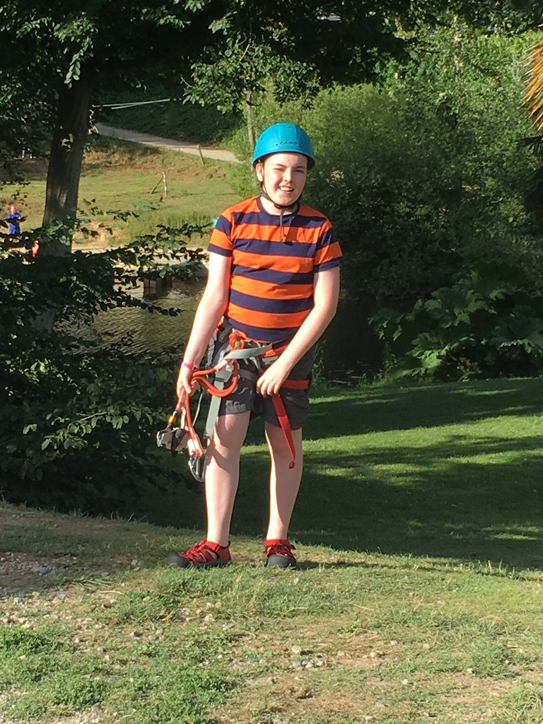 Boy in rope course/zip wire gear